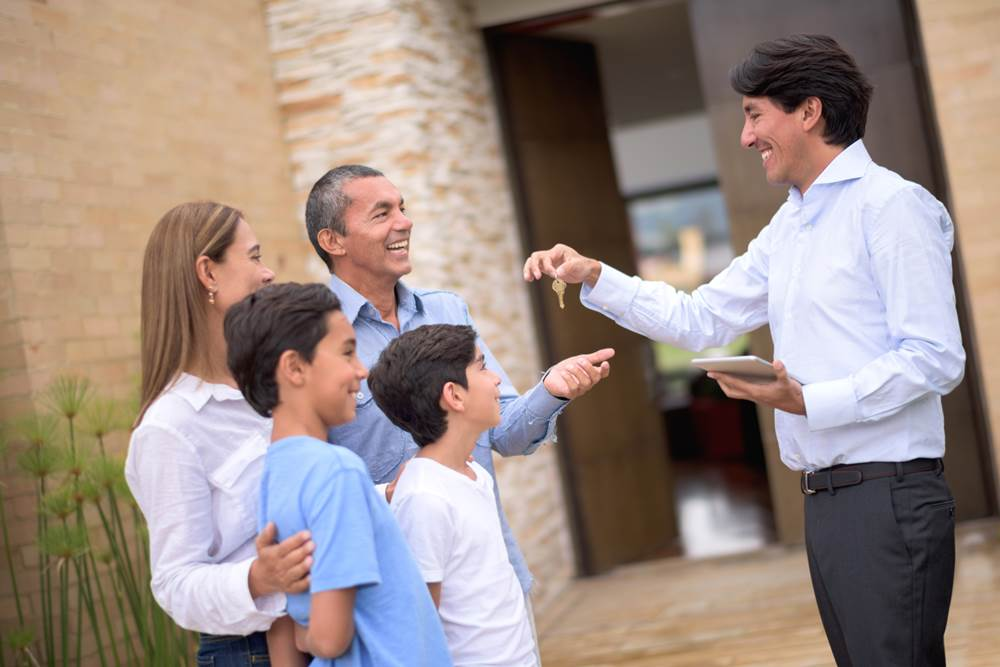 Real estate agent giving keys of their new house to a happy Latin American family
