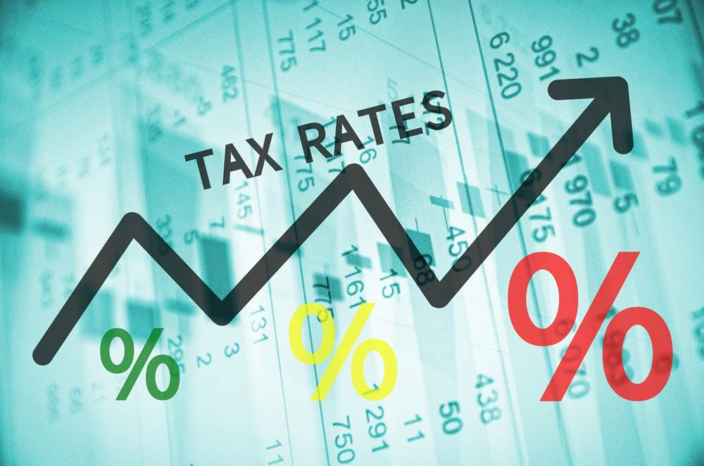 Text Tax rates on up trend arrow, with financial data visible on the background.
