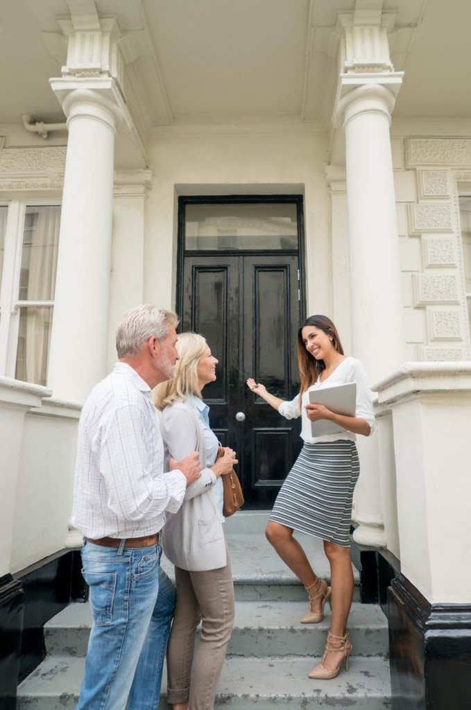 Happy couple buying a house and realtor showing them a property